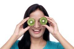 La giovane donna la ha coperta occhi di fette del kiwi Fotografie Stock Libere da Diritti
