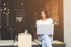 La giovane donna latina sta sedendosi con il computer portatile aperto nella caffetteria moderna del marciapiede Immagini Stock Libere da Diritti