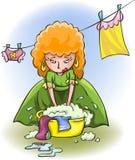 La giovane donna lava i vestiti Fotografia Stock