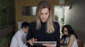 La giovane donna lavora dentro l'ufficio che sta con la compressa video d archivio