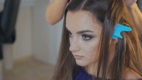 La giovane donna le che ottiene i capelli si è vestita nel salone di capelli video d archivio