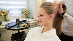 La giovane donna le che ottiene i capelli si è vestita nel salone di capelli stock footage