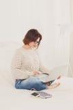 La giovane donna legge dal computer portatile a letto, alta chiave Immagine Stock