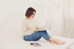 La giovane donna legge dal computer portatile a letto, alta chiave Fotografia Stock Libera da Diritti
