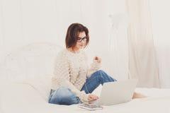 La giovane donna legge dal computer portatile a letto, alta chiave Immagini Stock Libere da Diritti