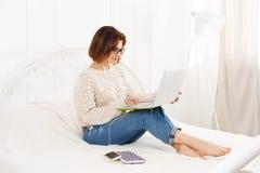 La giovane donna legge dal computer portatile a letto, alta chiave Fotografia Stock
