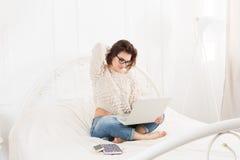 La giovane donna legge dal computer portatile a letto, alta chiave Immagini Stock