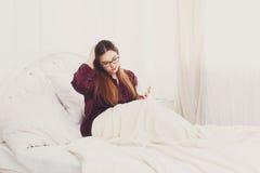 La giovane donna legge dal pc della compressa a letto, alta chiave Immagine Stock Libera da Diritti