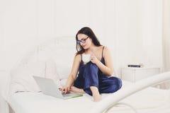 La giovane donna legge dal pc della compressa a letto, alta chiave Immagini Stock
