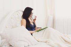 La giovane donna legge dal pc della compressa a letto, alta chiave Fotografie Stock Libere da Diritti
