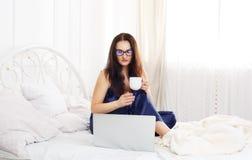 La giovane donna legge dal pc della compressa a letto, alta chiave Immagine Stock