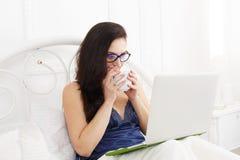 La giovane donna legge dal pc della compressa a letto, alta chiave Fotografia Stock Libera da Diritti