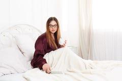 La giovane donna legge dal pc della compressa a letto, alta chiave Fotografie Stock