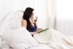 La giovane donna legge dal pc della compressa a letto, alta chiave Fotografia Stock
