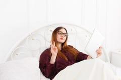 La giovane donna legge dal pc della compressa a letto, alta chiave Immagini Stock Libere da Diritti