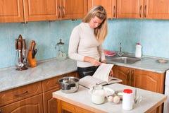 La giovane donna legge il libro di cucina Immagini Stock Libere da Diritti