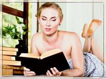 La giovane donna legge un libro che si trova su uno scrittorio davanti ad una finestra vecchio stile, concetto di lolita Immagine Stock
