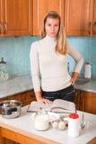 La giovane donna legge un libro di cucina Fotografia Stock Libera da Diritti