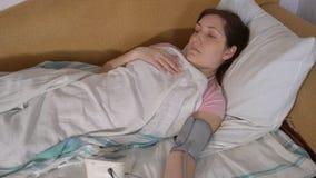La giovane donna a letto misura la pressione con il tonometer elettronico video d archivio