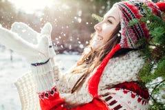 La giovane donna in maglione rosso getta la neve Attività di inverno fotografie stock libere da diritti