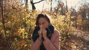 La giovane donna malata è condizione di starnuto nel parco nel giorno di autunno, facendo uso del fazzoletto stock footage
