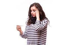 La giovane donna malata in sciarpa ed i vestiti domestici colpiscono l'esame del termometro fotografia stock libera da diritti