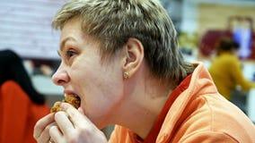 La giovane donna mangia gli alimenti a rapida preparazione nel ristorante del caffè Fotografie Stock