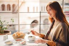 La giovane donna mangia l'alimento turco tradizionale dalla minestra di lenticchia immagine stock
