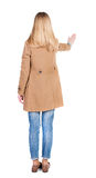 La giovane donna in mantello comprime su qualcosa Fotografia Stock