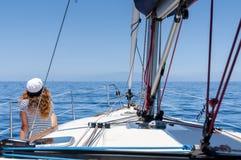 La giovane donna marina di stile sta sedendosi sulla barca e sta guardando in avanti Immagine Stock