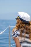 La giovane donna marina di stile sta sedendosi sulla barca e sta guardando in avanti Fotografia Stock Libera da Diritti