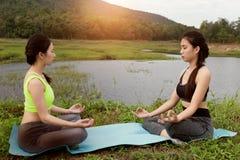 la giovane donna medita mentre pratica l'yoga all'aperto in parco, con riferimento a Fotografie Stock