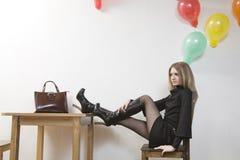 La giovane donna mette i suoi piedini sulla tabella Fotografia Stock