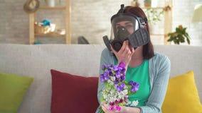 La giovane donna mette sopra un respiratore, prendente e fiutante i fiori video d archivio