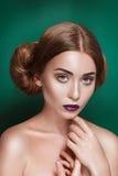 La giovane donna misteriosa attraente con il doppio panino dei capelli nell'acconciatura di principessa Leia guarda verso la macc Fotografia Stock