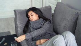 La giovane donna misura la temperatura che si siede sul sofà nella casa Sensibilità della donna infelice durante un virus o il fr archivi video