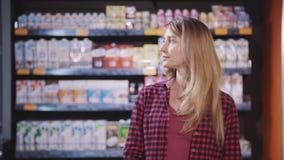 La giovane donna moderna è stante e pensante che alimento vuole comprare e cucinare per la cena video d archivio