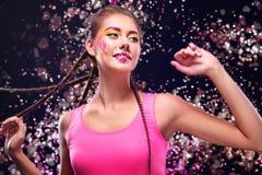 La giovane donna moderna con trucco di arte gode di di ascoltare la musica in cuffie Emozioni positive, svago Copi lo spazio Immagine Stock