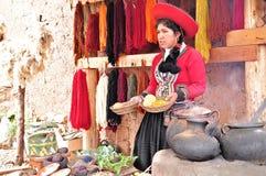 La giovane donna mostra e dice circa produzione dei vestiti. Immagini Stock