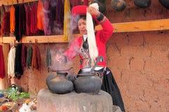 La giovane donna mostra e dice circa produzione dei vestiti. Immagine Stock