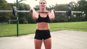 La giovane donna muscolare sta facendo gli esercizi con il bilanciere archivi video