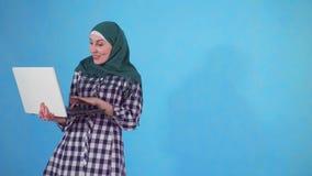 La giovane donna musulmana allegra utilizza un computer portatile ed impara circa la vittoria su un fondo blu stock footage