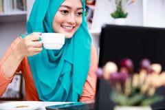 La giovane donna musulmana gode di di bere una tazza di tè fotografie stock