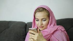 La giovane donna musulmana nel hijab rosa che si siede su un sofà in un caffè ed invia un messaggio di testo sul telefono cellula video d archivio