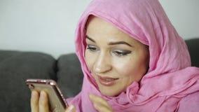 La giovane donna musulmana sta chiacchierando con i suoi amici telefono cellulare nelle mani di una donna araba che indossa un hi stock footage