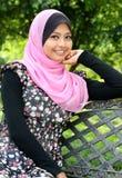 La giovane donna musulmana sta sedendosi sul banco   Immagini Stock Libere da Diritti