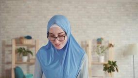 La giovane donna musulmana in un hijab con vista difficile mette sopra i vetri per la visione e gli sguardi intorno archivi video