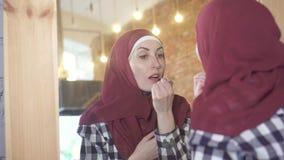 La giovane donna musulmana in un hijab davanti ad uno specchio dipinge le sue labbra archivi video