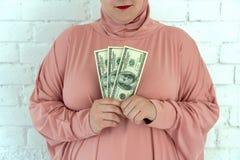 La giovane donna musulmana in vestiti rosa del hijab tiene di denaro contante nelle banconote del dollaro e del rosario in sue ma fotografie stock libere da diritti