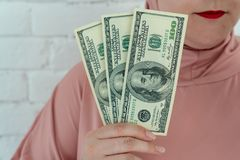 La giovane donna musulmana in vestiti rosa del hijab tiene di denaro contante nelle banconote a del dollaro in sue mani fotografia stock libera da diritti